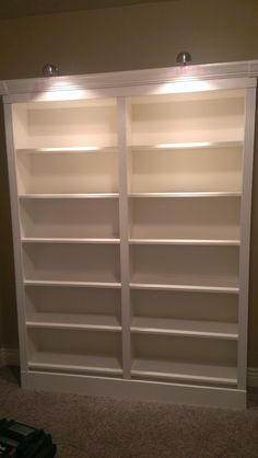 They're done!  Ikea Billy bookshelves dressed up with base and crown molding/lighting.