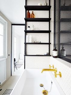 Bathroom with hexagonal tile mosaic across the floors, gold fixtures, and floating shelves