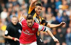 He's back: Mesut Ozil (left) holds off Jake Livermore during the Premier League match...