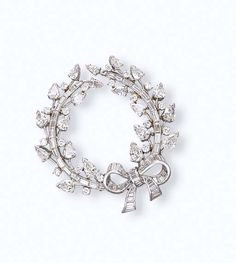 A DIAMOND BROOCH    Designed as a vari-cut diamond wreath enhanced by a baguette-cut diamond ribbon, mounted in platinum and 14k white gold, 5.3 cm wide
