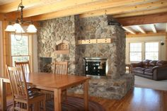 This stone fireplace is a centerpiece for this post and beam home. It is made up of a pass-through fireplace and a custom beehive brick oven... light ceiling and drywall to break up pine