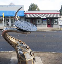 """Vancouver's newest piece of public art, """"The Visitor,"""" busts out of a manhole at West 23rd Street and Main. (The Columbian)"""