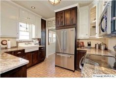 Two tone cabinets in kitchen... white upper, dark wood lower. (would have painted the cabinets above the fridge). by bessie
