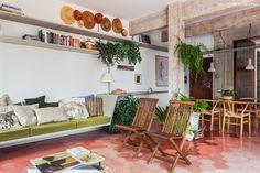 Móveis de concreto, madeira e piso de ladrilho hidráulico rosa na sala de estar desse apê no centro de SP.