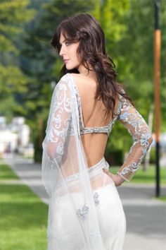An ensemble that steals limelight with lasting impression, magnificent White flowing net saree creatively enhanced with detail motif design, matched to classic full sleeve nude shade blouse. $665