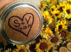 corkboard on mason jar lid displaying initials and date of wedding