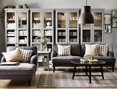 A living room with a grey two-seat sofa, chaise lounge and a black round coffee table. Combined with four grey glass-door cabinets.
