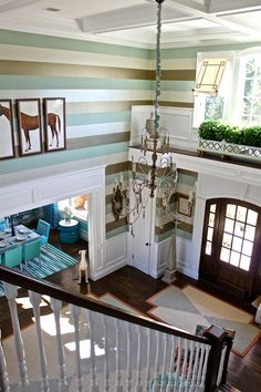 2012 Hampton Designer Showhouse: double story entry designed by Kentucky designer Lee W. Robinson. With a soothing color scheme referencing the coastline location, Robinson took full advantage of the height of the space with a fabulous Osborne & Little stripe wallpaper, the horizontal direction effectively enhancing the soaring ceiling.