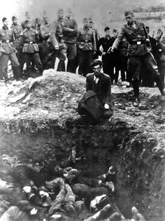 """This photo, one of the most widely distributed after the war, shows a German soldier shooting a Ukrainian Jew during a mass execution in Vinnytsia, Ukraine, sometime between 1941 and 1943. This image is titled """"The last Jew in Vinnitsa"""", the text that was written on the back of the photograph, which was found in a photo album belonging to a German soldier. The German is no more than 20 years old. The youth in the black uniform in the background is no more than 16."""