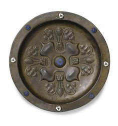 GERMAN, NUREMBERG, SECOND HALF 15TH CENTURY  DISH WITH LION HEADS AND VINES      with indistinct ink inscription to the reverse; together with a brass alms dish centred by a band containing a foliate motif, German, probably Nuremberg, 16th century  brass, with blue and white champlevé enamel roundels