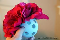 Easy way to make hanging flower balls. Wiffle balls from dollar store,  dollar store fake flowers, pull the stems off the flower, hot glue around the circle in the wiffle ball, press flower into the hole making sure the bottom of the flower, keep going until the ball is full of flowers, then hang with a ribbon.