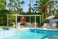This palm springs home has a large pool, blue tile interior, a fountain feature, a mid-century modern pavilion, simple outdoor furniture, and tropical landscaping.