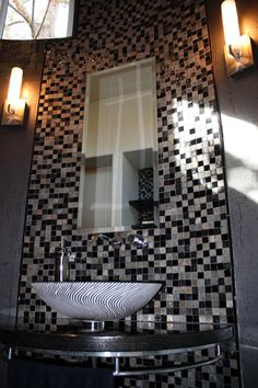 The black and silver mosaic tile backsplash extends to the ceiling in this contemporary powder room. Sconces on either side illuminate the space, while a tall mirror visually expands the area. A black and white swirled vessel sink completes the glam look.