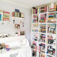 Quarto bem clean, com escrivaninha branca, rádio retrô, vitrola floral e uma estante com muitos livros e funko pop.