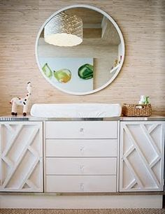 round mirror over console with grasscloth wall