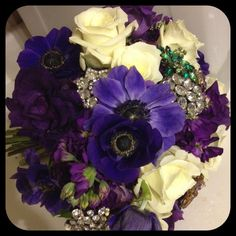 purple anemome, white roses, stocl and purple lizzie. brooches compliment