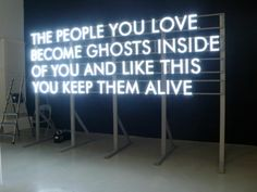 """Neon sign: """"The people you love become ghosts inside of you and like this you keep them alive"""""""
