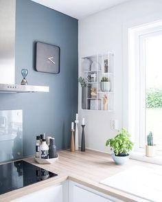 Cuisine épurée, mur gris bleuté et plan de travail en bois clair