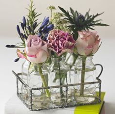 Six Vintage Style Glass Bottles With Fresh Flowers. Six vintage style glass bottles held in a delightful metal basket with a feminine selection of vintage colour pink and purple blooms.