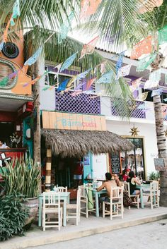 Sayulita, Mexico - A small and charming surf town full of colorful, cobblestone streets. Love the papel picado strung between palm trees!