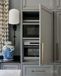 Gray-painted cabinetry conceals the microwave. - Photo: Lisa Mowry / Design: Clay Snider