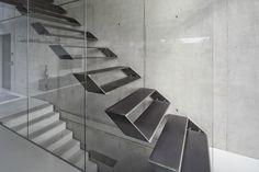 Die Treppe, die auf der Ostseite ins Obergeschoss führt, ist eines der Highlights des Wohnhauses. Um eine möglichst große Transparenz in Längsrichtung der Fuge zu gewährleisten, wurden die Treppenstufen als Stahlkisten in die Betonwand gedübelt, was dazu führt, dass sie in Längsrichtung nur eine minimale Ansichtsbreite aufweisen. Auf diese Weise scheinen sie zwischen Beton und Glas zu schweben. https://www.homify.de/ideenbuecher/30223/das-haus-der-zukunft