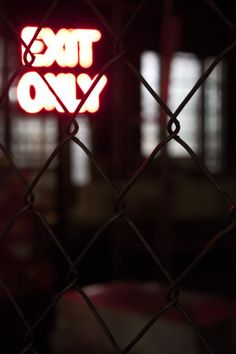This photo shows depth of field because the fence is in focus and the background isnt. I like it because of the lit up exit only sign in the background.