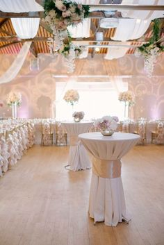 Blush and Gold wedding floral decor in a small space.  Hanging ceiling oversized frame with floral details as well as large oversized centrepieces placed strategially throughout the table space.  Small, but elegant centrepieces are placed on hightop tables to tie them into the rest of the room.  Florals created by Akiko Floral Artistry.  Photo Credit;  Milton Photography.  #phalaenopsis #orchids #blush #gold #blushandgold #ivory #tulips #roses #peonies #hydrangea #wedding #floral #decor