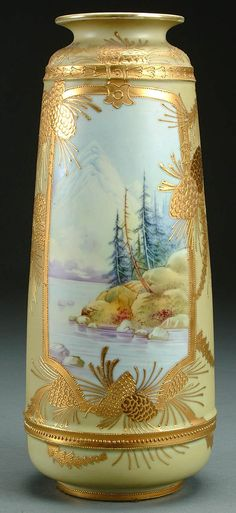 A NIPPON MOUNT FUJI GILT AND SCENIC DECORATED PORCELAIN VASE CIRCA 1900 WITH A MOUNTAIN LAKE SCENE FRAMED IN A CARTOUCHE OF RAISED GILT ACORNS