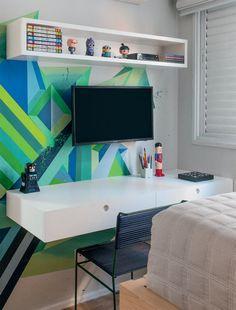 Suspensa e com gavetas largas, a escrivaninha foi fixada no canto da parede. Cadeira da FJ Pronto pra Levar.