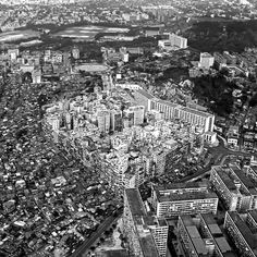 At its peak, the Kowloon Walled City was home to 33,000 people in just two hectares of land—the size of about two rugby fields—making it the densest place on Earth at the time. It was a hastily put together conglomerate of tiny apartments, one on top of the other, caged balconies slapped onto the sides and connected through a labyrinth of damp, dark corridors.