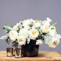 White garden roses with silver brunia and dusty miller. Yes please! – @gothamflorist All in our Ribbed Luster Black Vase.