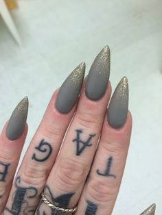 Matte gray with gold glitter stiletto nails. ✨