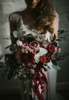 a textural winter wedding bouquet with foliage, red blooms, cascading amaranthus and dahlias
