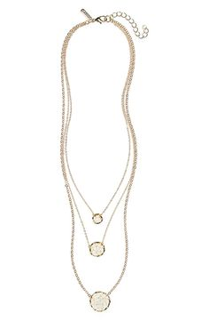 Accessorizing with this layered necklace that features shimmering crystal beads, a delicate goldtone wire, and pendants.