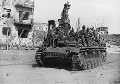 Wehrmacht infantry in Stalingrad's devastated streets riding on StuG III Ausf. B assault gun. Assault guns were the guardian angels of both infantry and tanks caught in anti-tank fire.
