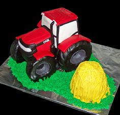 Tractor body made from chocolate cake frosted with vanilla buttercream, covered with fondant; tractor tires made from cereal treats covered with fondant.  Haystack is also cake covered with fondant.