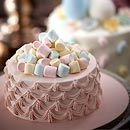 A pile of pastel marshmallows is a sweet topper for this elegantly  piped pink cake.