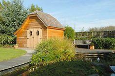 Un abris de jardin en bois au bord d'une piscine biologique.