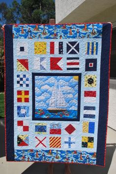 Custom nautical quilt for my sister. All A-Z Nautical Flags and her boat appliqued in the center. Made with scraps fabrics in the red, blue, yellow, and white represented in the flags. By Michele Cassidy
