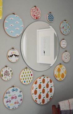 Bastidores de diversos tamanhos com tecidos em várias estampas, fazem uma composição interessante ao redor do espelho redondo.