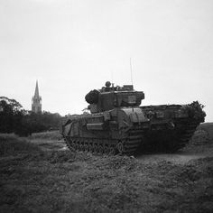 A Churchill tank moves up towards the village of Tourville in preparation for an attack on Hill 112 16 July 1944.