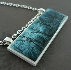 I created this pendant by baking a photograph into a handmade polymer clay base and sealing with resin. It is strung from a handmade ball chain.  The photograph features the silhouette of barren trees as the sun shines through on an early morning.