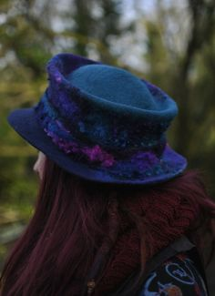 Serendipity is a handmade felt trilby. Hand felted with luxurious wools in richly hand dyed shades. Organic merino, BFL & Wensleydale wools. The curls are nuno felted in from teeswater fleece procured from the eco farm down the road. Measures approx 10cm high. Each hat is a beautifully crafted, solidly felted piece that will be your companion for life, if you let it. Love it and it will love you back! All original designs created by hand, from raw materials each time, exclusively at…