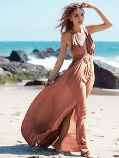 Endless Summer Look Into the Sun Maxi - Sun goddess maxi in a crinkly crepe with a deep V-neck, adjustable rope halter, and stretchy smocked empire waist with geo cutout detailing below. Raw edges. We love tying the slit, and creating a knotted hem to change up the look - at Free People Clothing Boutique