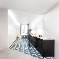 The kitchen features a blue geometric floor, adding a splash of colour to the otherwise muted furnishings.