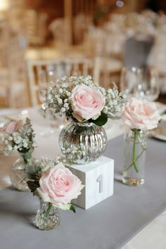 Blush pink roses in mercury silver vases on a top table at a wedding - this is a lovely idea if you are looking for pink wedding decorations