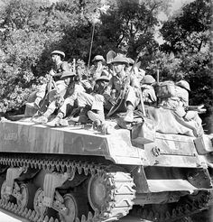 "Infantrymen of the West Nova Scotia Regiment ride on ALBERTA, a Sherman tank of ""A"" Squadron of the Calgary Regiment during the advance from Villapiano to Potenza, Italy, on 18 September 1943."