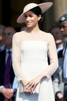 Prince Harry and Meghan Markle Make First Appearance After Royal Wedding. Meghan wears white dress and big white hat.