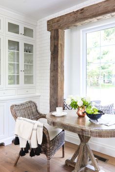 White lake house kitchen featuring a rustic beam breakfast nook area with a window seat, subway tile and blue and white accent pillows.